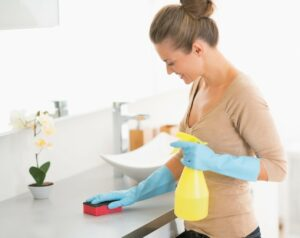 Housewife cleaning desk in bathroom