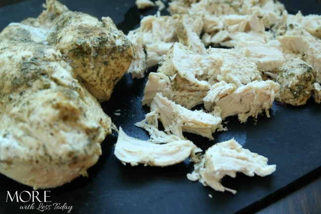 shredding chicken to make Fiesta Lime Poached Chicken