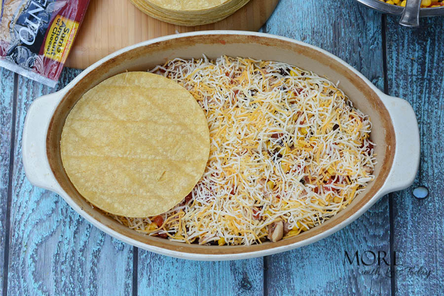 adding the cheese on and layering corn tortillas to make Four Cheese Bake recipe