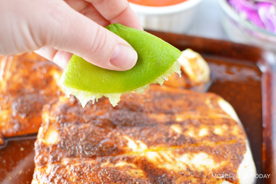 squeezing a lime on cod fish for fish tacos