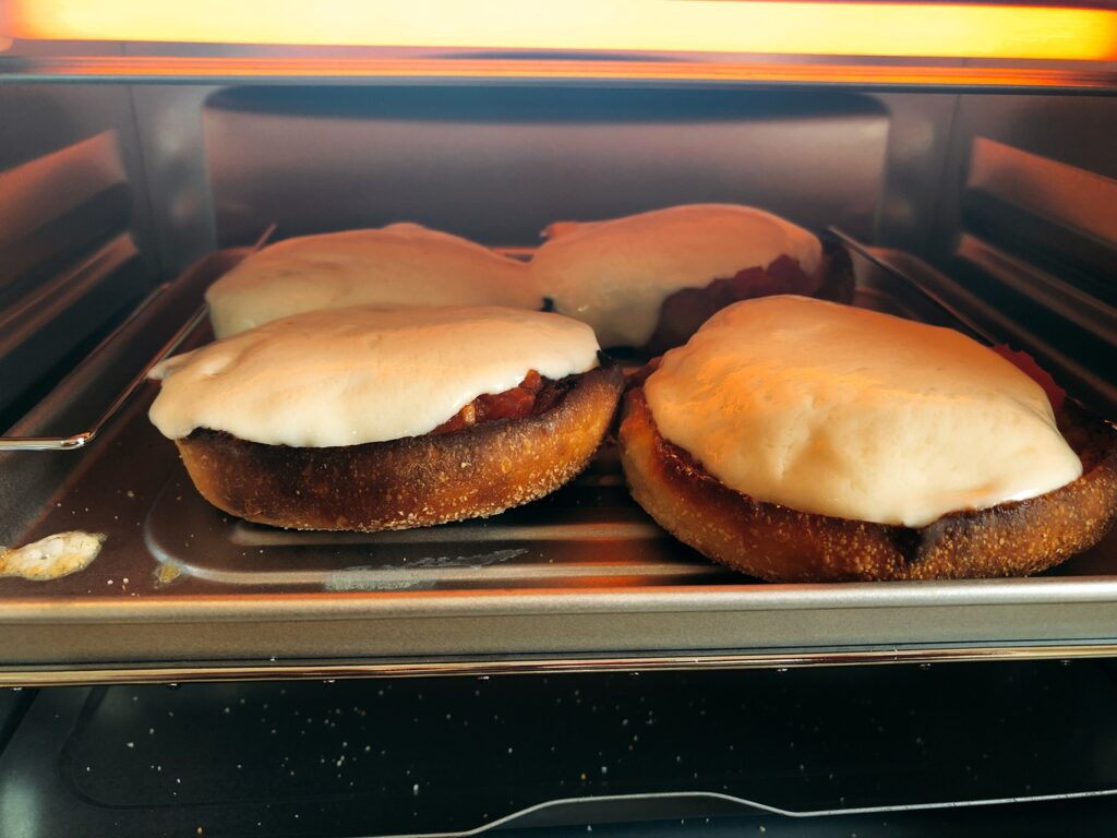 melting mozzarella cheese on Bays English Muffins in a toaster oven