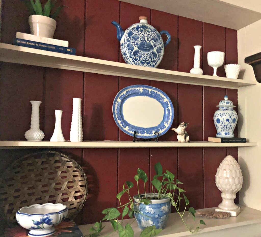 shelves with the backing painted red with blue and white decor