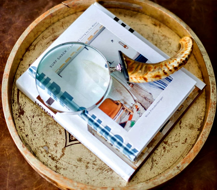 decorative tray with a book and a magnifying glass