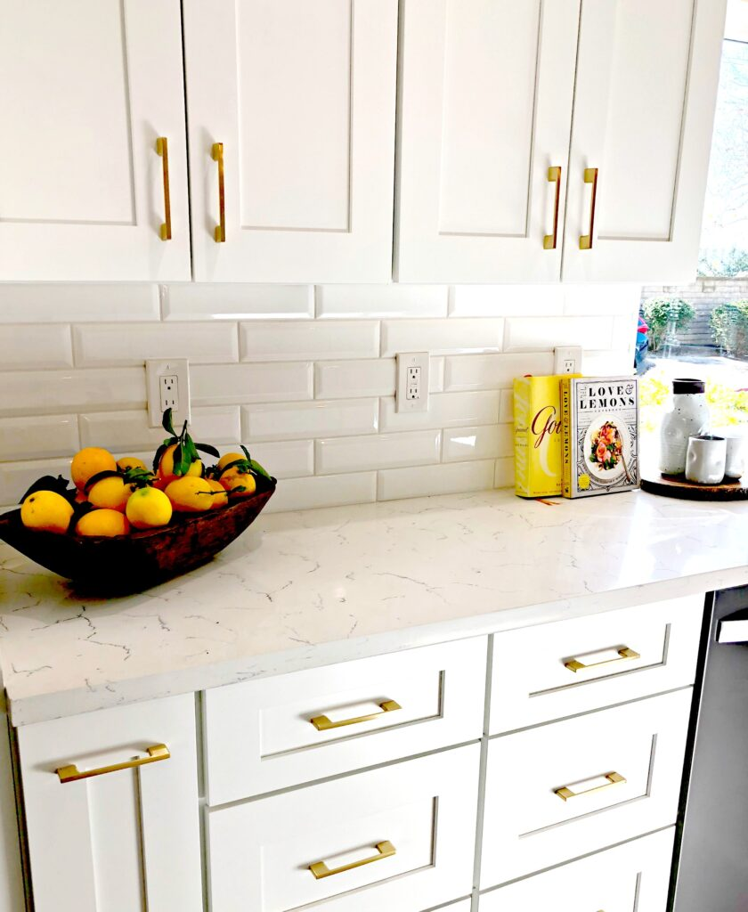 white kitchen cupboards with gold hardware and a bowl of lemons on the countertop