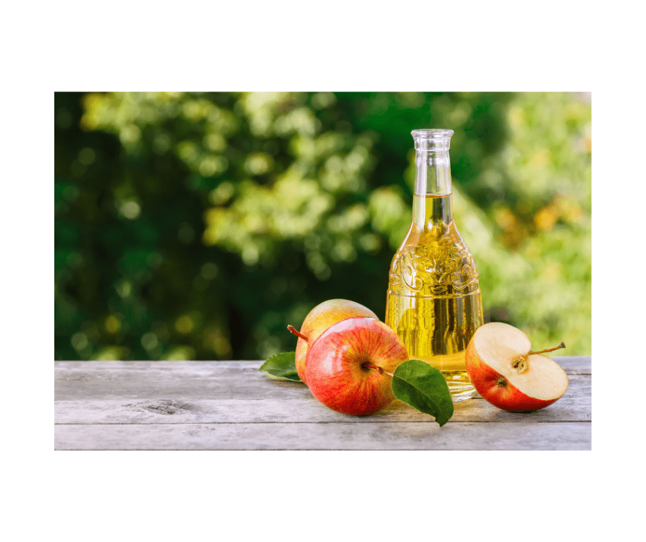 photo of apple cider vinegar in a carafe with 3 apples on a counter