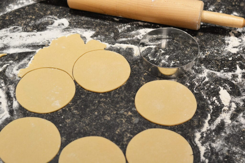 rolling pin rolling out dough for mini apple pies