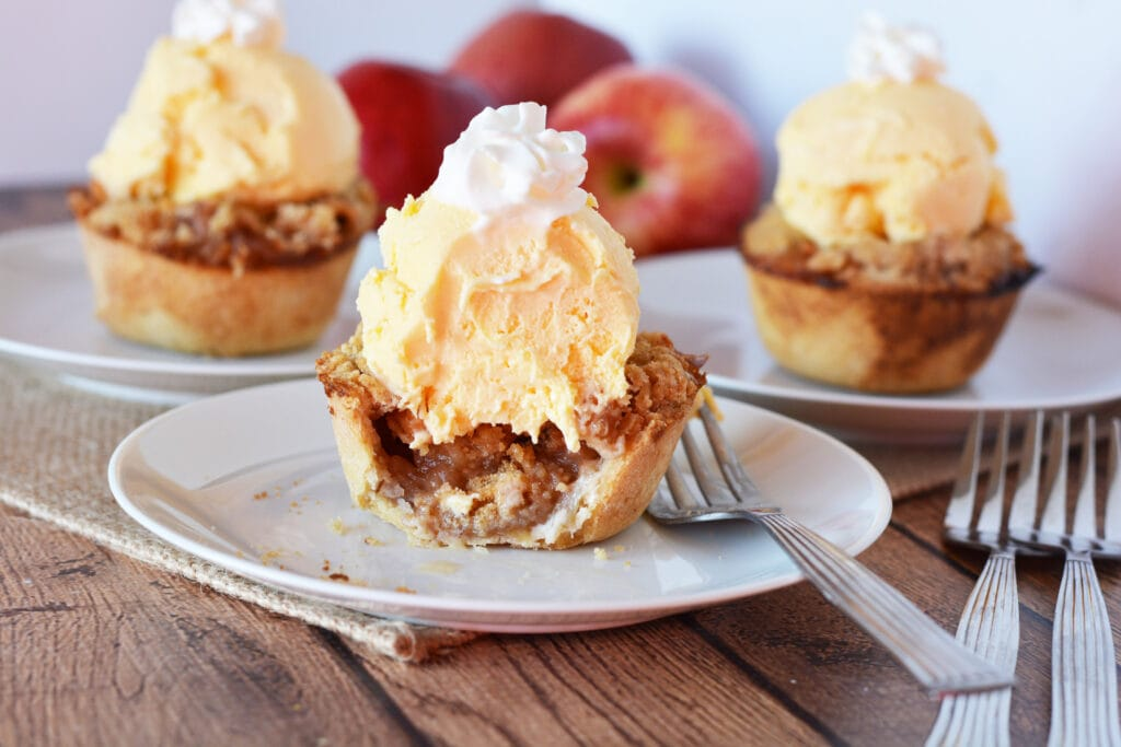 mini apple pies with ice cream and whipped cream topping