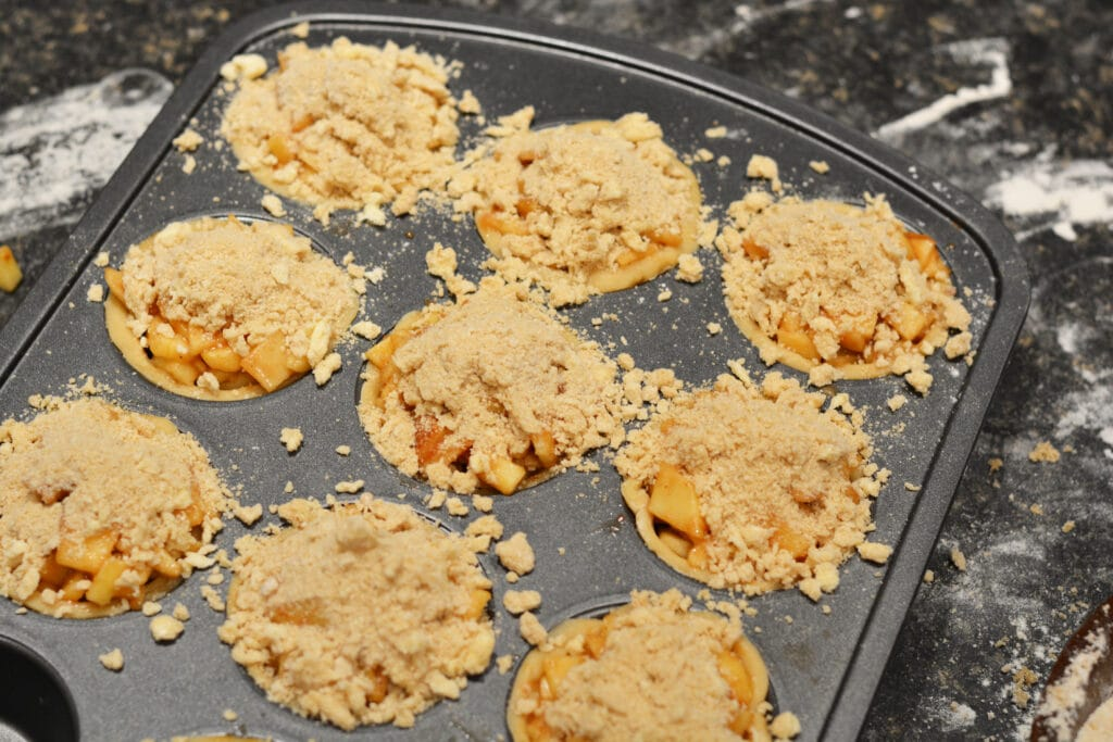 sprinkling topping on mini apple pies