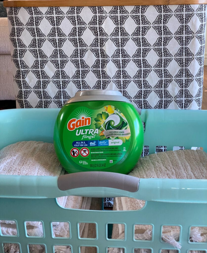 Gain Ultra Flings with Oxi Boost and Febreze for Large Loads in a laundry basket on top of towels with a black and white hamper behind it