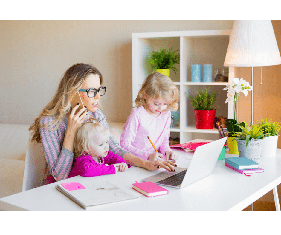 photo of a busy mom on the phone and on the computer with two small girls at her side and on her lap