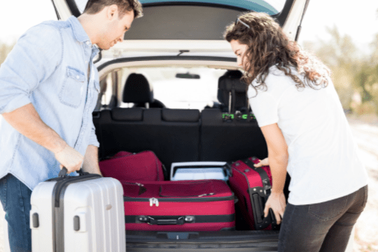 woman and man packing suitcases in the car