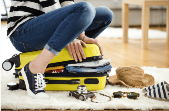 woman sitting on a suitcase trying to close it