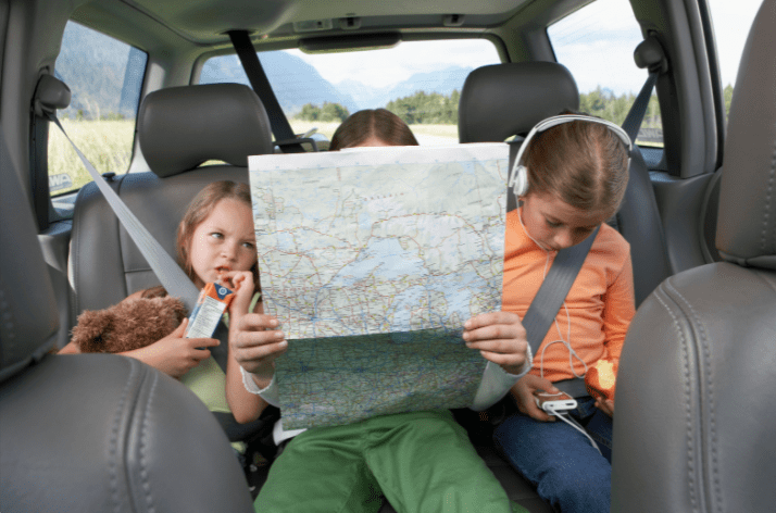 kids on a road trip looking at a map