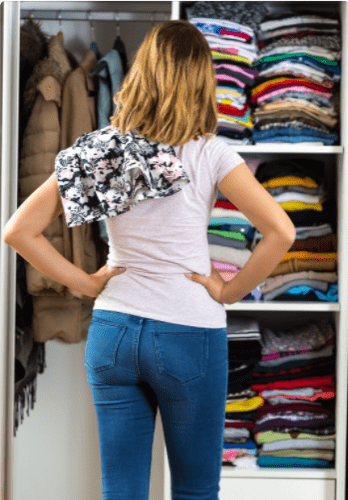 women looking in her closet full of folded clothing