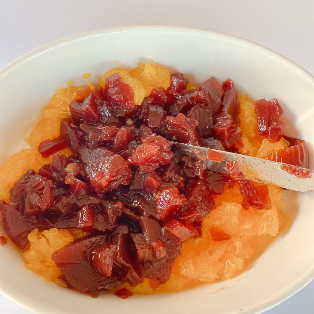 mixing cranberry sauce and mandarin oranges